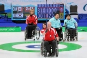 Jim Armstrong curling with Ina Forrest holding his chair and Sonia Gaudet in the background on the ice